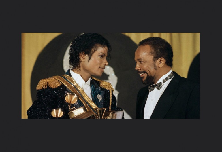 Michael Jackson holds several Grammy awards as he stands with Quincy Jones on Feb. 28, 1984. (Doug Pizac/Associated Press)