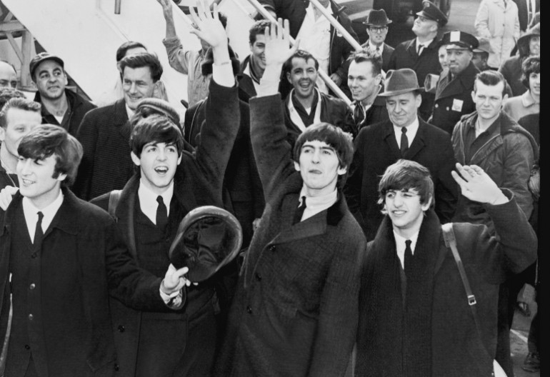 The Beatles begin the British Invasion when landing in New York City in 1964.